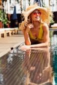 Szexi fiatal nő a fürdőruhát és a szalma kalap üdülőhely napsütéses napon