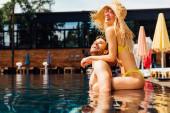 sexy šťastný pár objímající v bazénu za slunečného dne