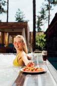 szexi lány fürdőruhát a vörösbor és eper a medencében