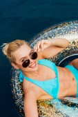 smiling girl in swimsuit and sunglasses lying on swim ring in swimming pool