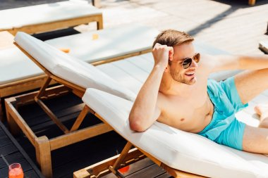 Happy shirtless man in sunglasses lying on lounger at resort stock vector