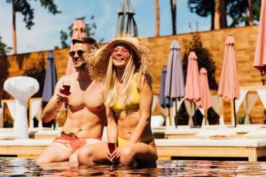 sexy couple holding glasses of red wine and smiling in swimming pool