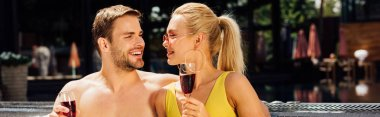 Panoramic shot of sexy couple holding wine glasses with red wine and looking at each other at resort stock vector