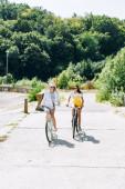 šťastná blondýnka a brunetka na kole v létě