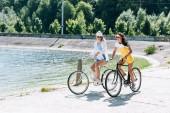 Veselá blondýnka a bruneta dívky v létě na kolech u řeky