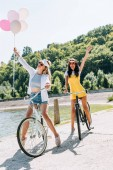 happy blonde and brunette friends riding bikes with balloons near river in summer