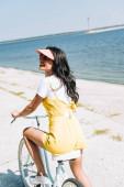 šťastná brunetka jezdila na kole blízko řeky v létě