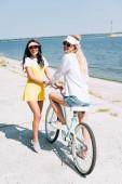 šťastná blondýnka a brunetka s cyklistou poblíž řeky v létě