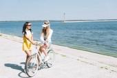 Veselé blondýny a bruneté dívky s cyklistou poblíž řeky v létě