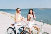 šťastná blondýnka a brunetka na kole se zmrzlinou u řeky v létě