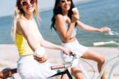 selektivní zaměření šťastné blondýny zobrazující zmrzlinu při jízdě na kole s přítelem