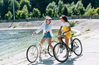 Happy blonde and brunette girls with bikes looking at each other near river in summer stock vector