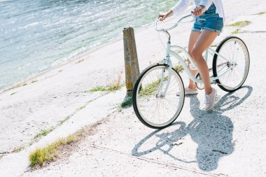 partial view of girl riding bike near river in summer