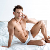 glücklicher Mann, der auf dem Bett sitzt und mit dem Smartphone spricht
