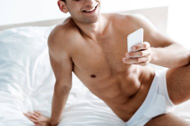 Cropped view of cheerful shirtless man using smartphone in bedroom stock vector