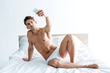 handsome and shirtless man taking selfie in bedroom