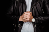 cropped view of stylish young man in leather jacket with clenched hands isolated on black
