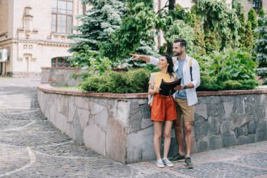 happy man pointing with finger while holding map and standing with girl