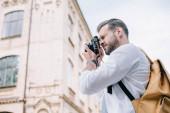 Niedrigwinkel-Ansicht des gutaussehenden Mannes, der Foto macht, während er Digitalkamera verwendet