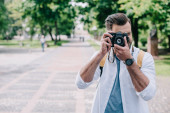 man covering face while taking photo on digital camera