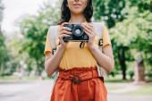 oříznutý pohled mladé ženy držící digitální fotoaparát vně