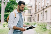 handsome bearded tourist holding map near building