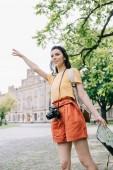 šťastná žena gestikulace při držení mapy v blízkosti budovy