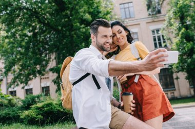 selective focus of happy man talking selfie with attractive woman near building