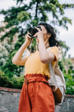 Low angle view of girl holding digital camera while taking photo stock vector