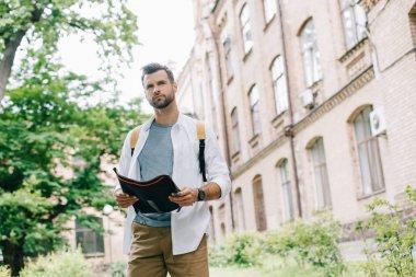 handsome bearded traveler holding map near building
