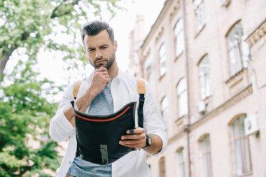 pensive bearded traveler holding map near building