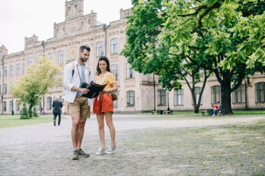 KYIV, UKRAINE - MAY 28, 2019: handsome man and attractive girl standing near building with map
