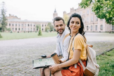 happy woman and man holding paper cups and map