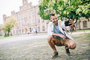 Cheerful bearded man taking selfie on digital camera near building stock vector