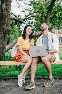 happy young woman sitting on bench near man using laptop
