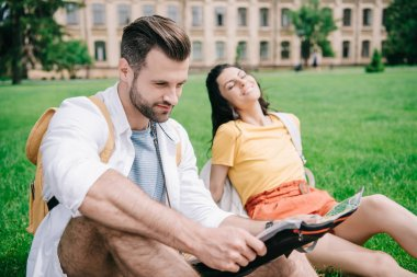 selective focus of happy man holding map near woman sitting on grass