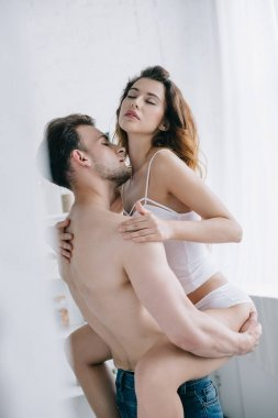 handsome boyfriend holding attractive girlfriend with closed eyes in apartment