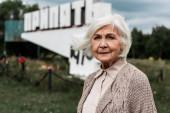 Pripyat, Ucraina - 15 agosto 2019: donna anziana in piedi vicino monumento con lettere pripyat