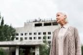 Pripjat, Ukrajina-15. srpna 2019: pohled na starší ženu stojící poblíž budovy s hotelem polissya v Černobylu