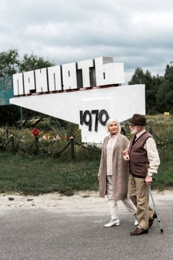 PRIPYAT, UKRAINE - AUGUST 15, 2019: retired husband and wife walking near monument with pripyat letters stock vector