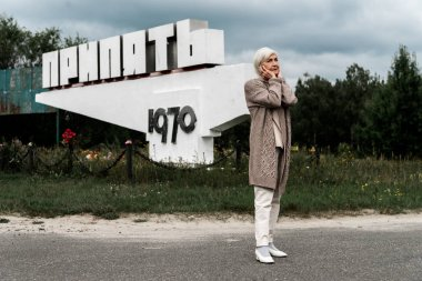 PRIPYAT, UKRAINE - AUGUST 15, 2019: retired woman standing near monument with pripyat letters and covering ears stock vector