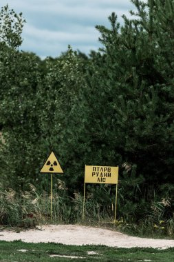 PRIPYAT, UKRAINE - AUGUST 15, 2019: chernobyl zone with yellow warning signs near green trees stock vector