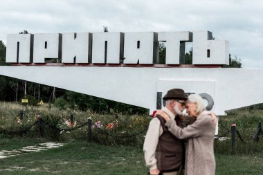 PRIPYAT, UKRAINE - AUGUST 15, 2019: selective focus of monument with pripyat letters near senior couple hugging outside stock vector