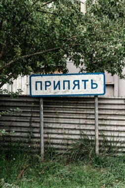 PRIPYAT, UKRAINE - AUGUST 15, 2019: sign with pripyat lettering near fence and trees stock vector