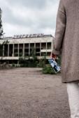 Pripyat, Ukraine - 15. August 2019: abgeschnittene Ansicht einer Rentnerin mit Schwarz-Weiß-Foto in der Nähe eines Gebäudes in Tschernobyl