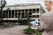 Pripyat, Ukraine - 15. August 2019: selektiver Fokus der Frau mit grauen Haaren halten Foto in der Nähe von Gebäude mit Schriftzug in Tschernobyl