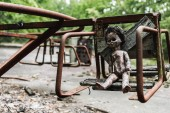 burnt baby doll on abandoned carousel in chernobyl