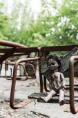 selektiver Fokus der schmutzigen Babypuppe auf verlassenen Karussell in Tschernobyl