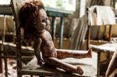 selektivní zaměření špinavé a spálené dětské panenky na dřevěném křesle ve škole