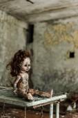 opuštěná a spálená dětská panenka na špinavém stole